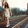 girl walks along railroad